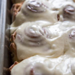 close up photo of frosted cinnamon rolls in a pan
