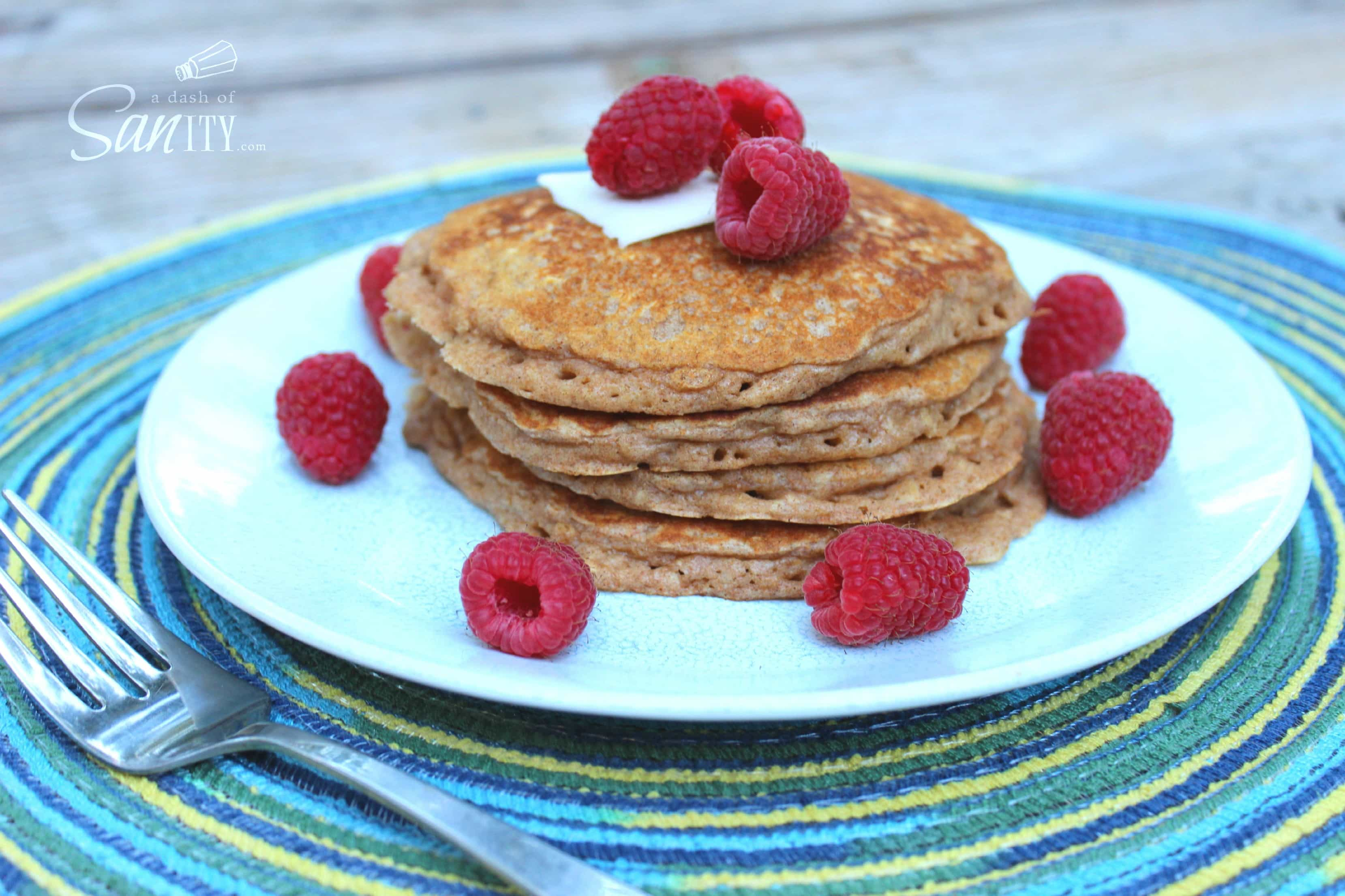 Whole Wheat and Oatmeal Pancakes in a stack on a plate with fresh raspberries