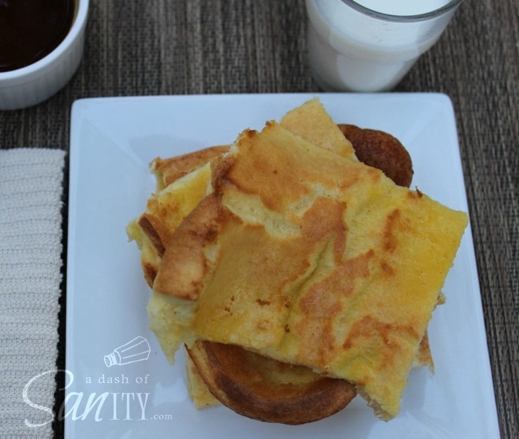 German Pancakes squares served in a stack on a square plate with a glass of milk