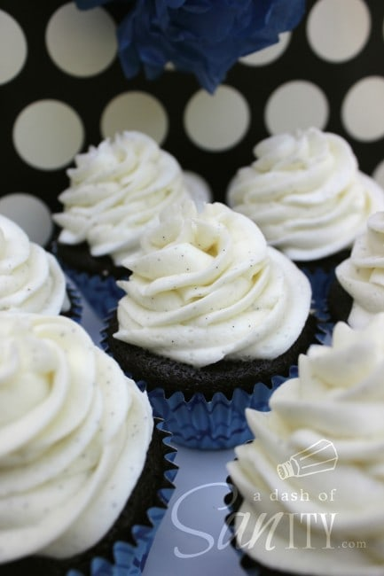 chocolate cupcakes in wrappers with piped vanilla buttercream frosting