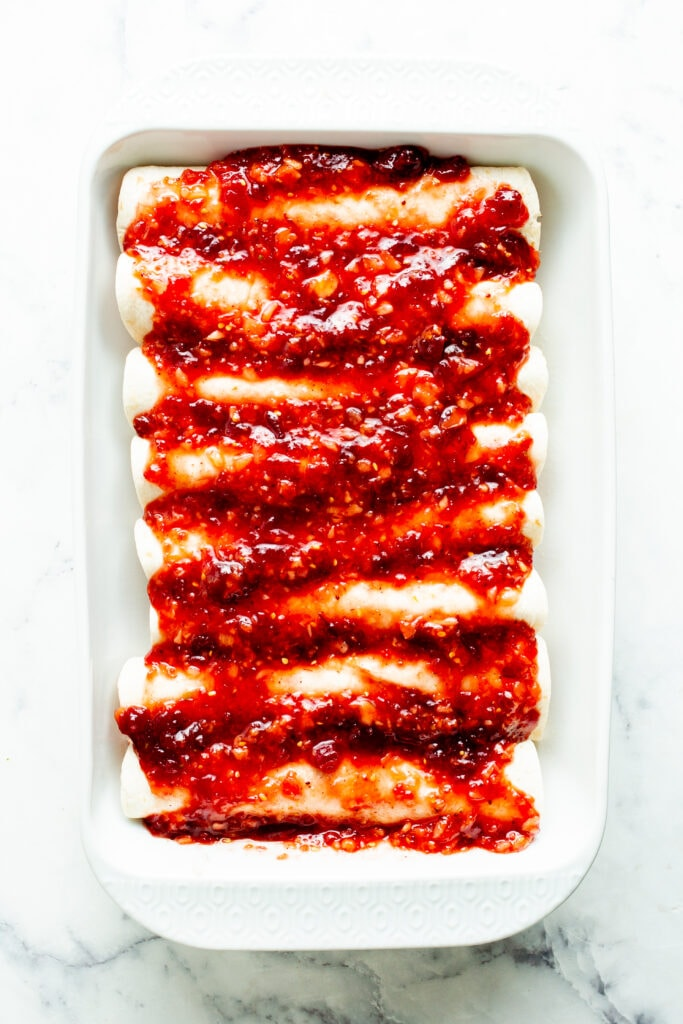 Enchiladas prepared in a baking dish with sauce on top