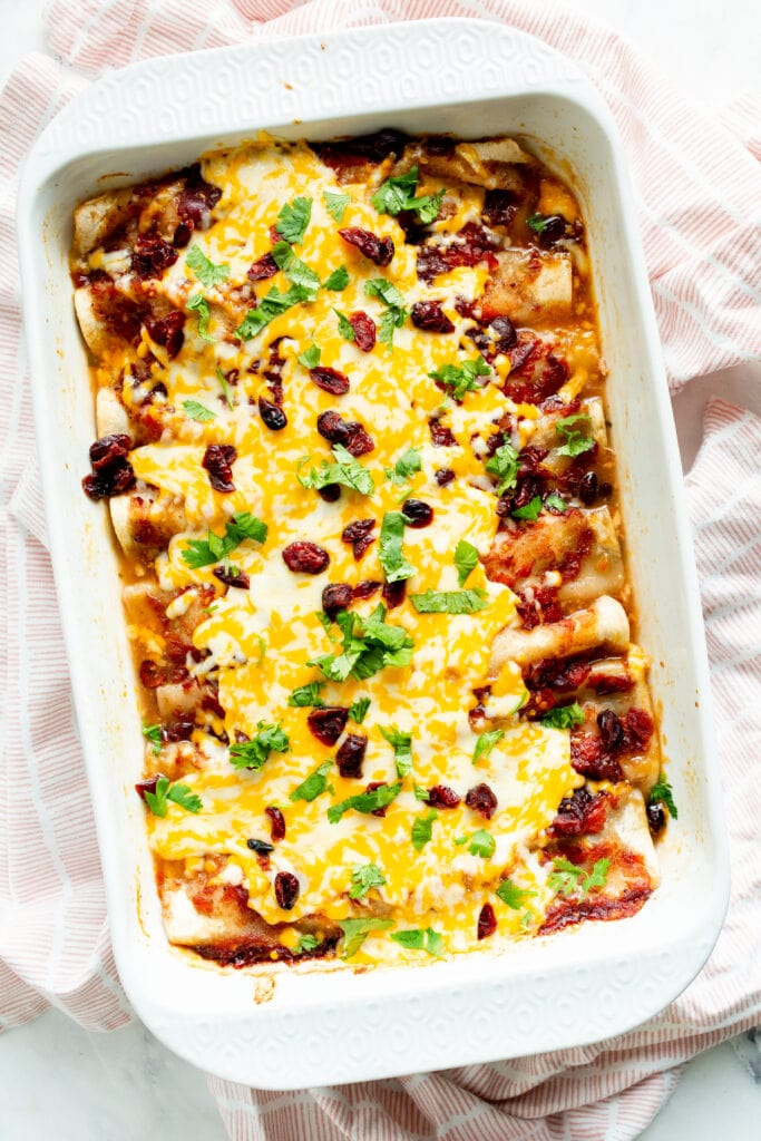 Baked enchiladas with toppings in baking dish viewed from above