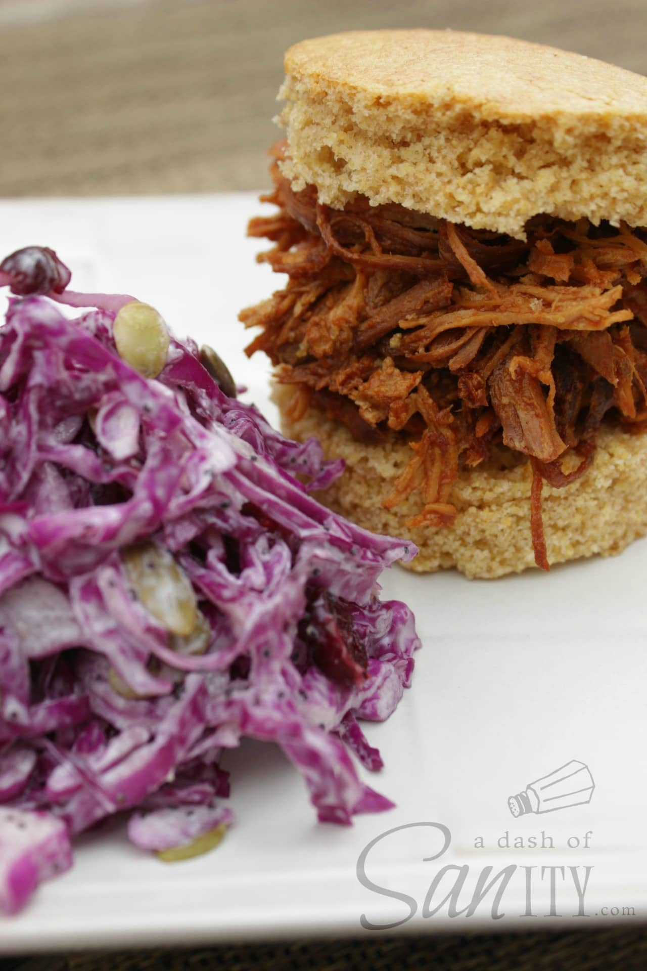 Barbeque Chicken served on sliced cornbread bun on a plate with a serving of Healthy Cole Slaw