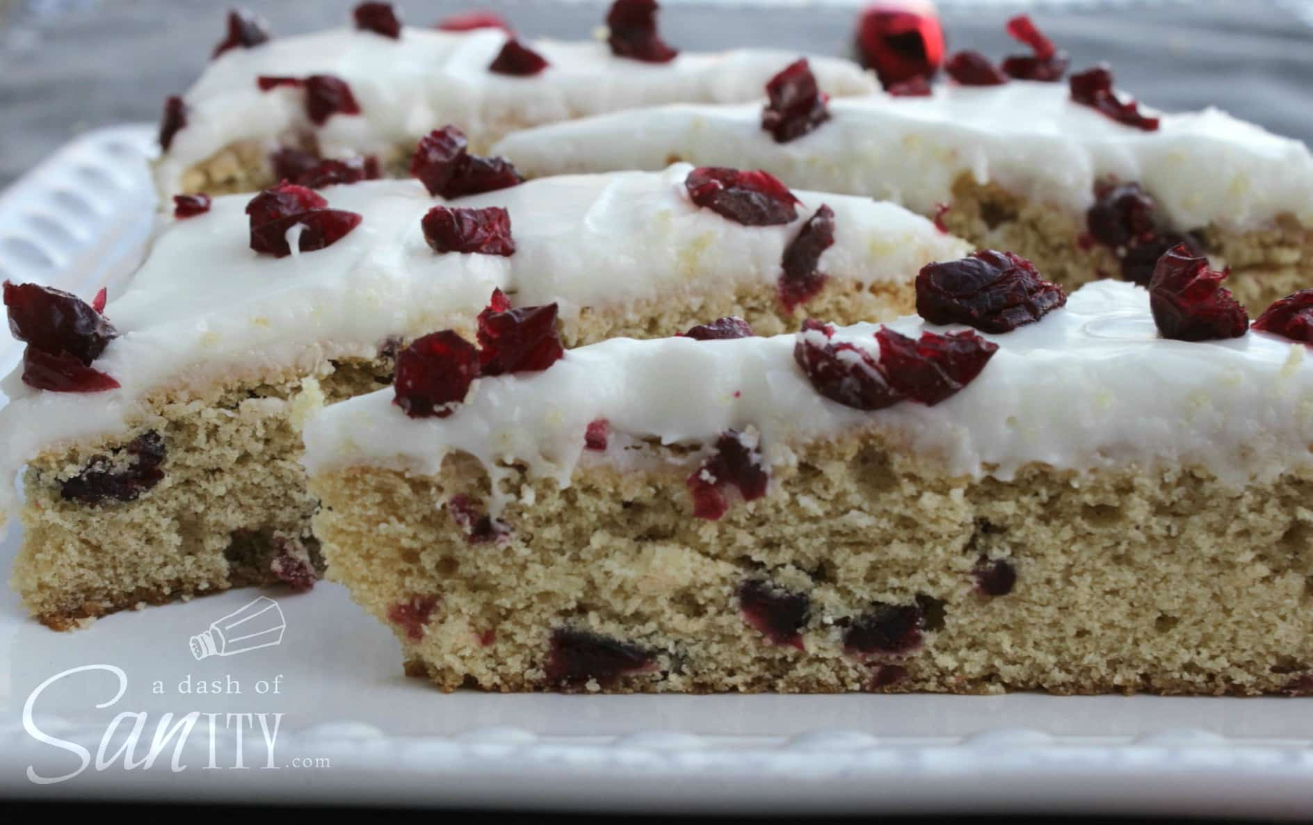 Blissful Cranberry Bars topped with dried cranberries and icing on a plate