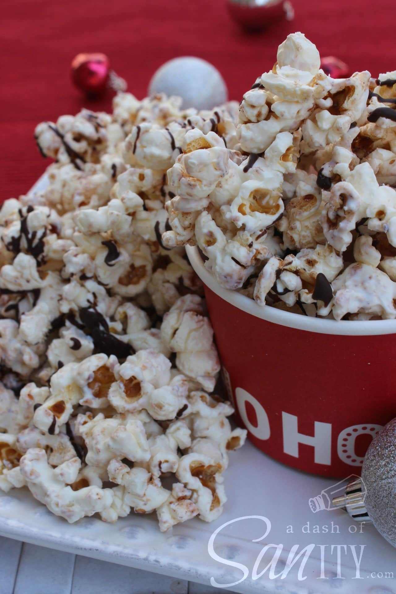 """Cinnamon White Chocolate Kettle Corn in a bucket that says """"ho ho ho"""", popcorn spilling out of bucket onto a plate"""