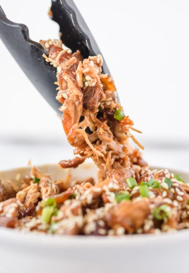 close-up photo of tongs grabbing shredded chicken
