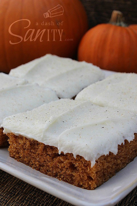 Pumpkin Bars with Cream Cheese Frosting on a plate with pumpkins in background