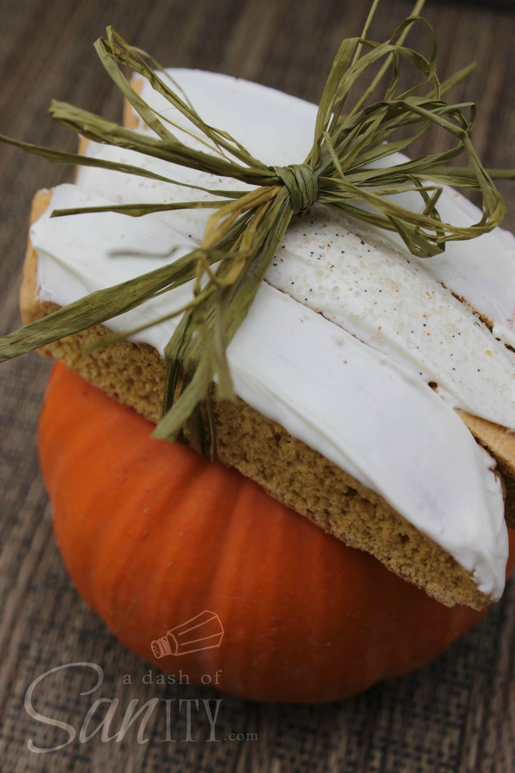 Pumpkin Ginger Biscotti with icing tied together, posed on top of a mini pumpkin