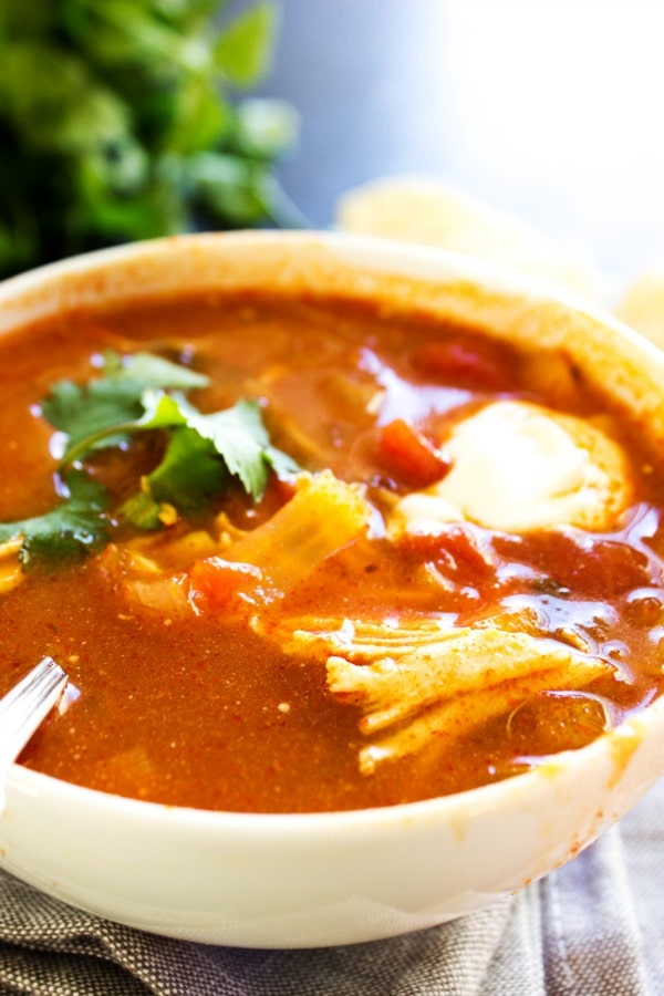 photo of tortilla soup garnished with cilantro served in a bowl