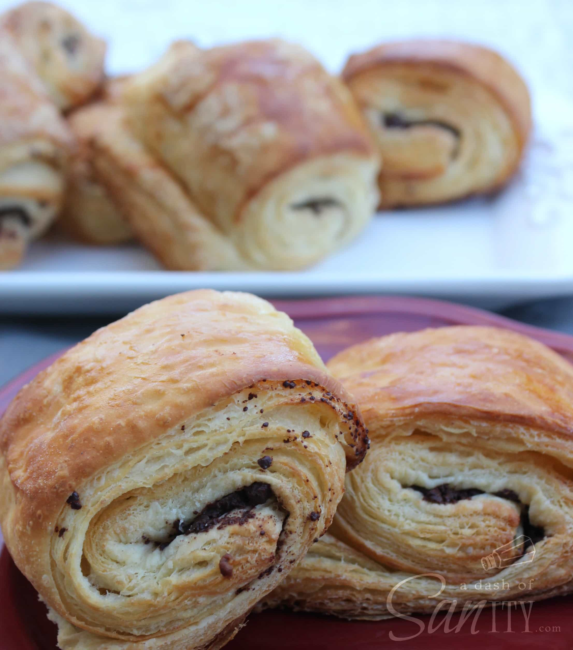 2 Chocolate Croissants served on a plate up close, with serving tray of Chocolate Croissants in background