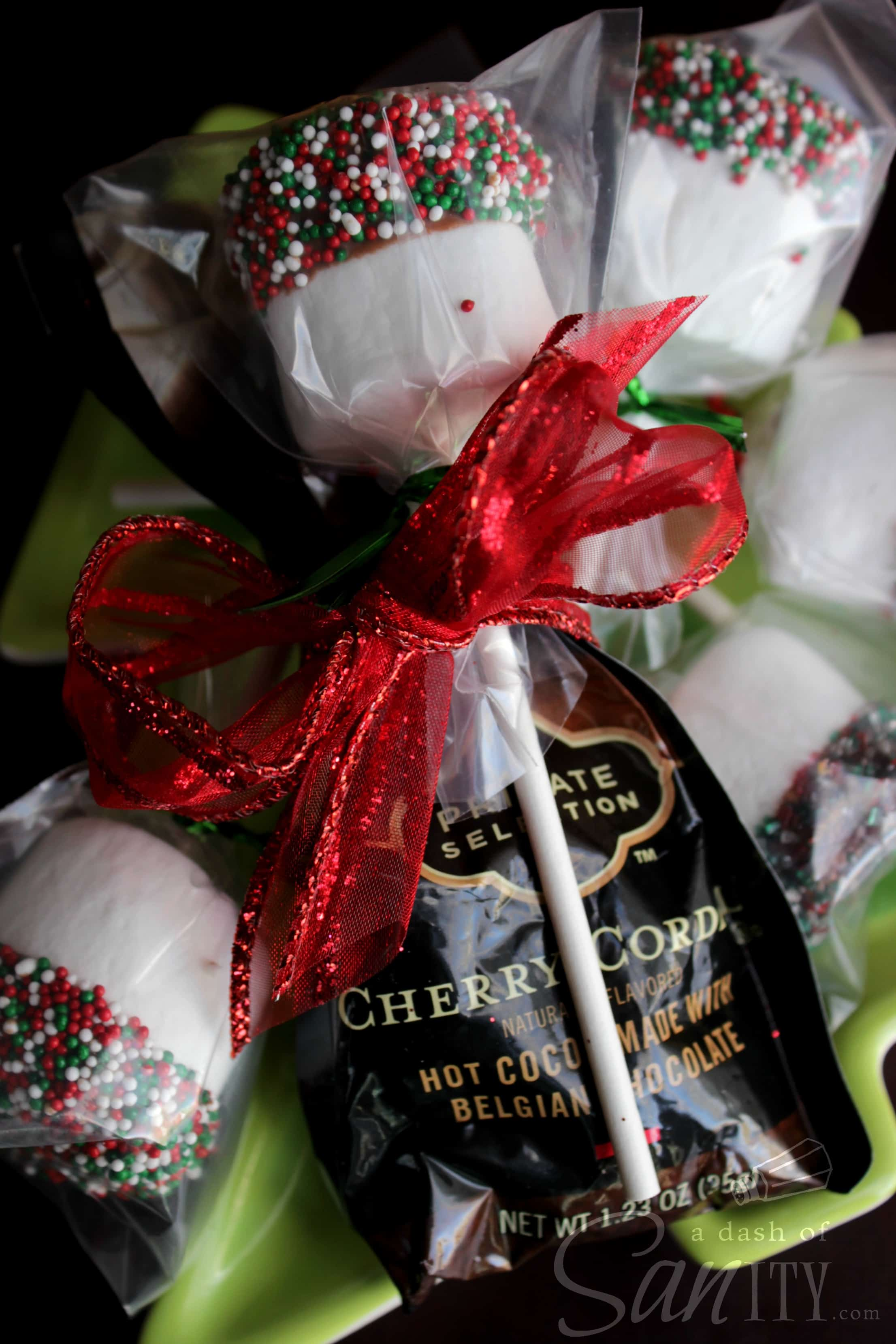 Marshmallow Hot Chocolate Dippers, marshmallows dipped in chocolate and red, white and green spinkles, wrapped in a clear bag with red ribbon and a packet of hot chocolate mix