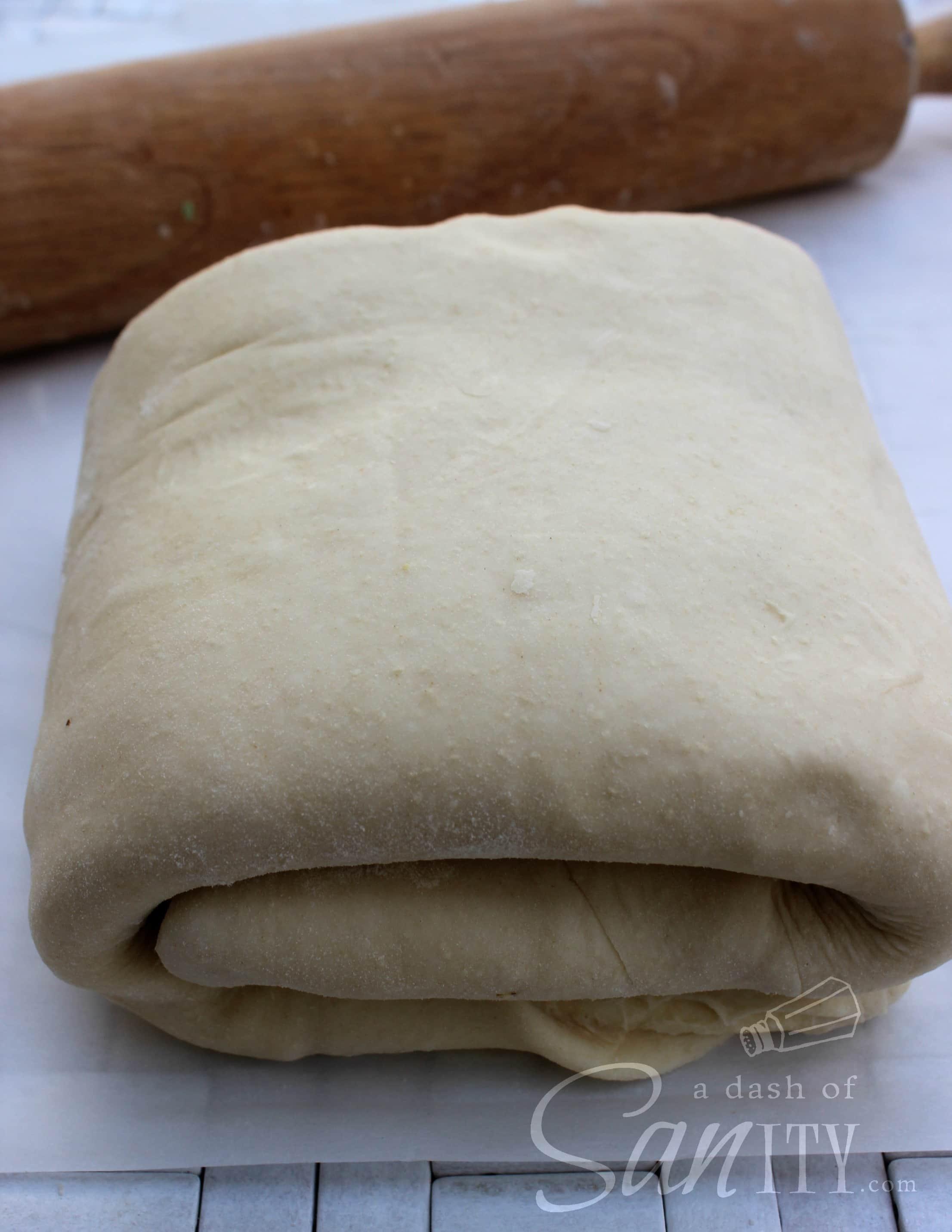 croissant dough folded into a square on parchment paper