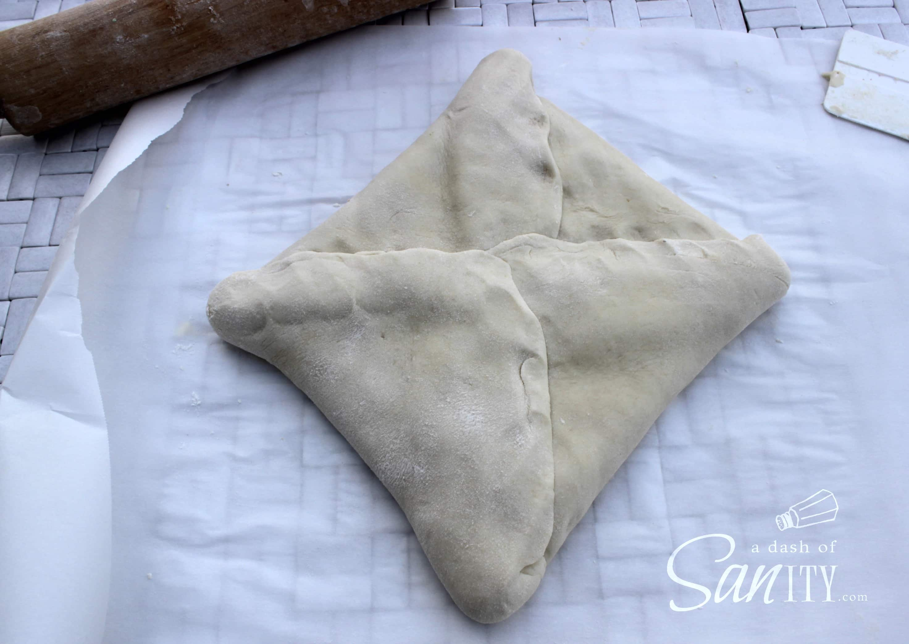 croissant dough on parchment folded around the butter square with seams pressed together