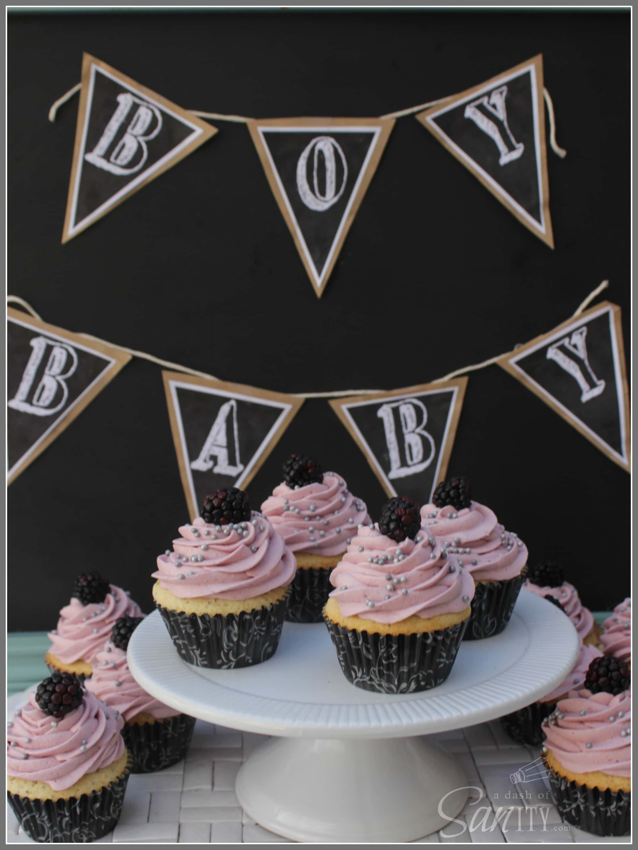 """'Lemon-Poppy Seed Cupcake with Blackberry White Chocolate Buttercream on a cake stand and counter, with a banner above that reads """"BABY BOY"""""""