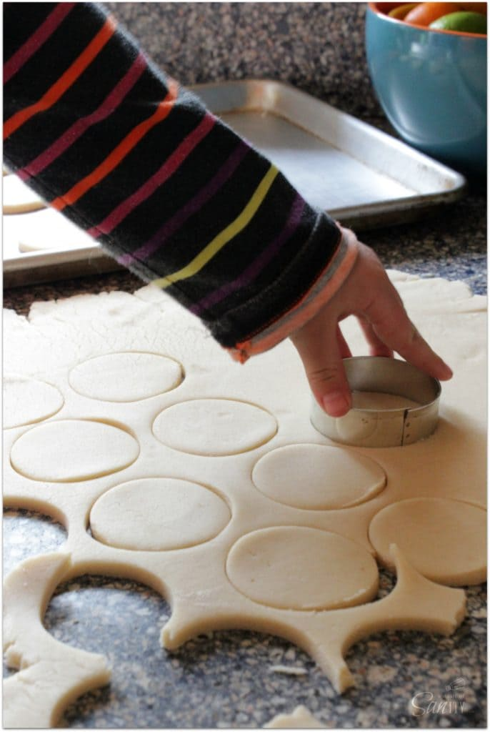 photo of cutting out tagalong cookie dough with round cookie cutter on counter