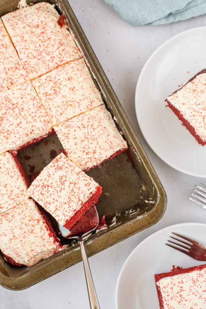 overhead photo of a red velvet cake in a pan with slices being removes