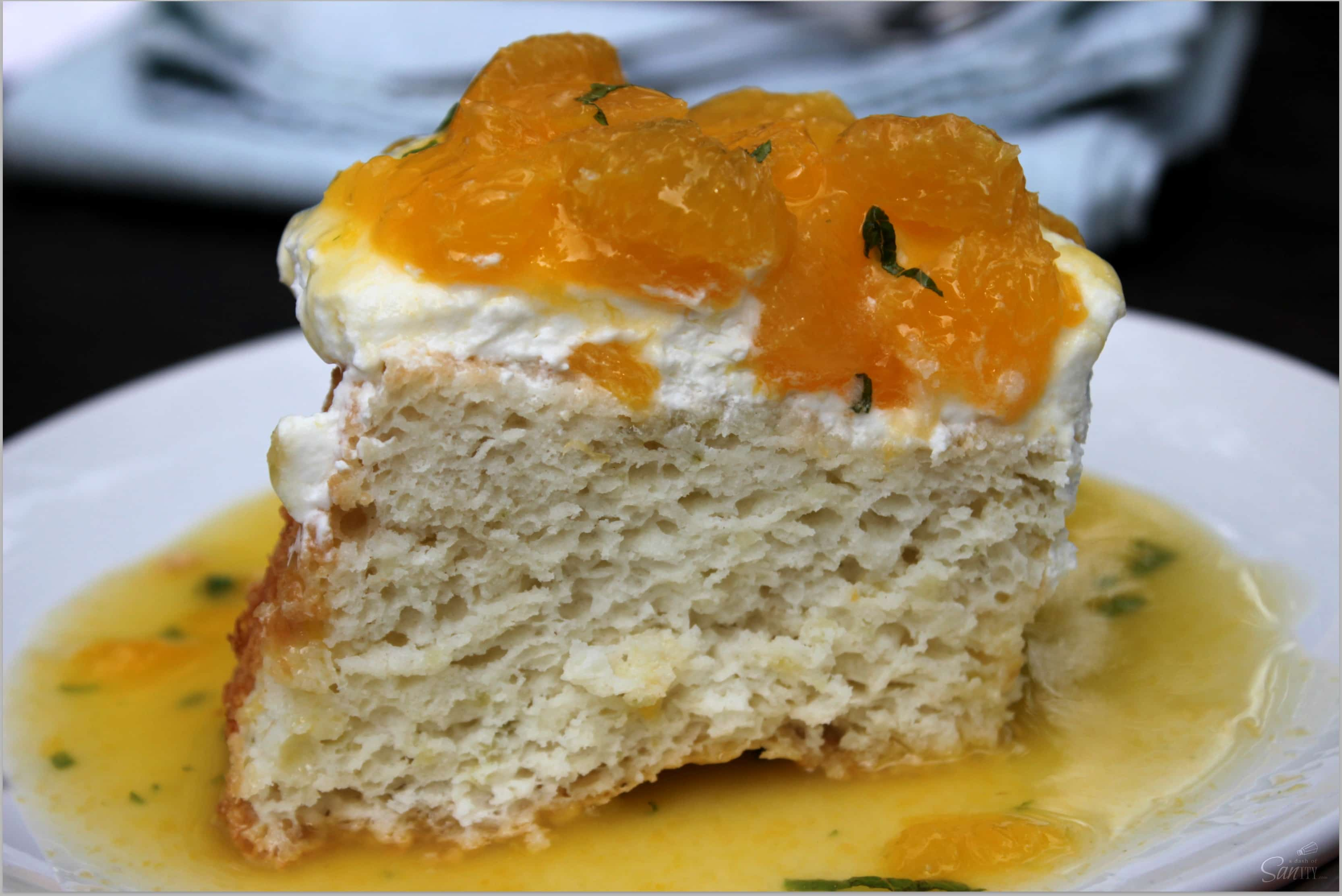 Citrus Angel Food Cake Topped with Fresh Oranges and Mint is a classic cake made with non-traditional twist. It is the perfect mix of sweet and tangy.