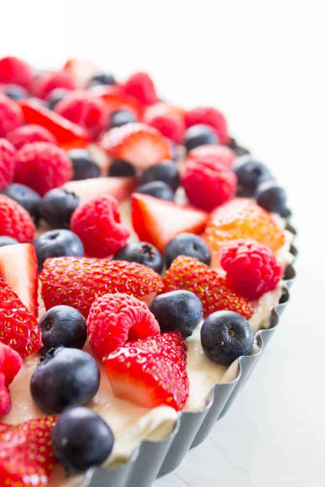 side view of Simple Fruit Tart in pan with strawberries, blueberries and raspberries