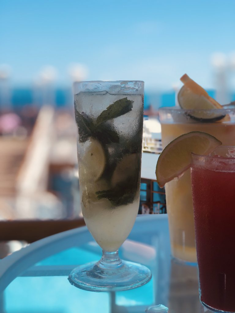 photo of virgin mojito and other drinks on a glass table on cruise ship deck