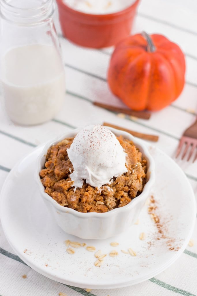 Pumpkin Crisp Pie in a small white serving bowl topped with whipped cream, next to a glass of milk