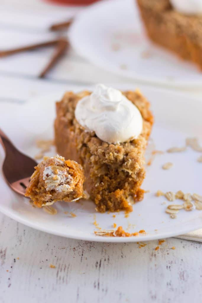 Pumpkin Crisp Pie slice on a plate, fork with bite on it. whipped cream on top