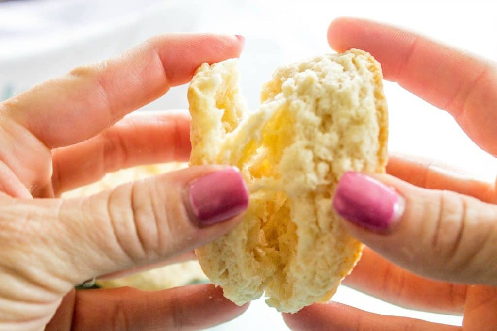 photo showing hands pulling apart a biscuit, with flakey layers inside