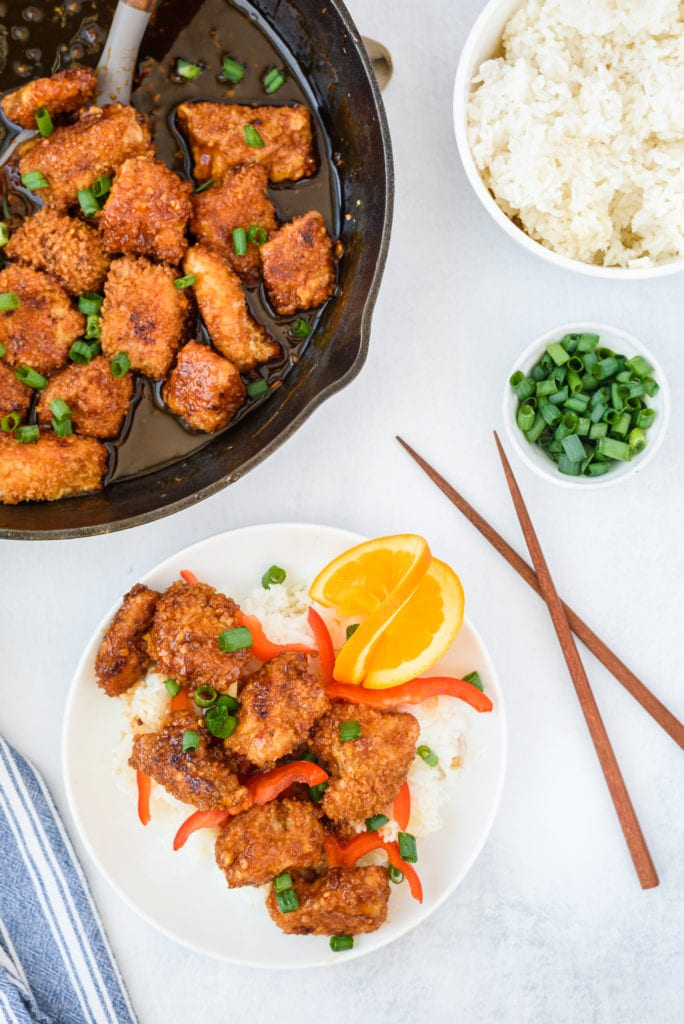 overhead photo of a plate of orange chicken with a skillet and bowl of rice