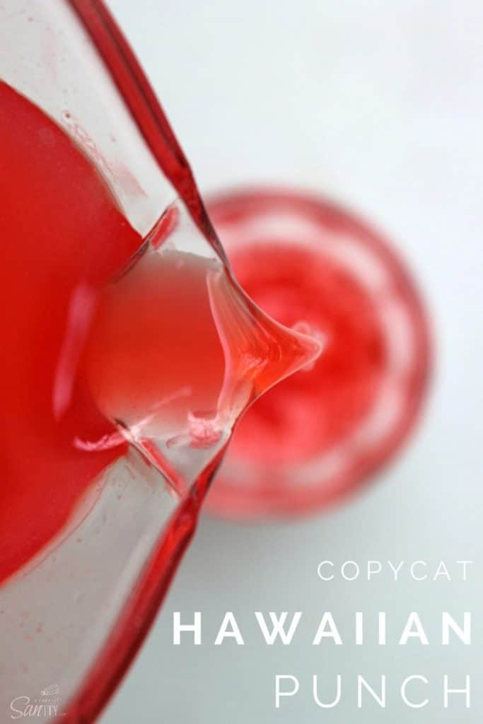 Copycat Hawaiian Punch in a glass pitcher being poured into a glass cup