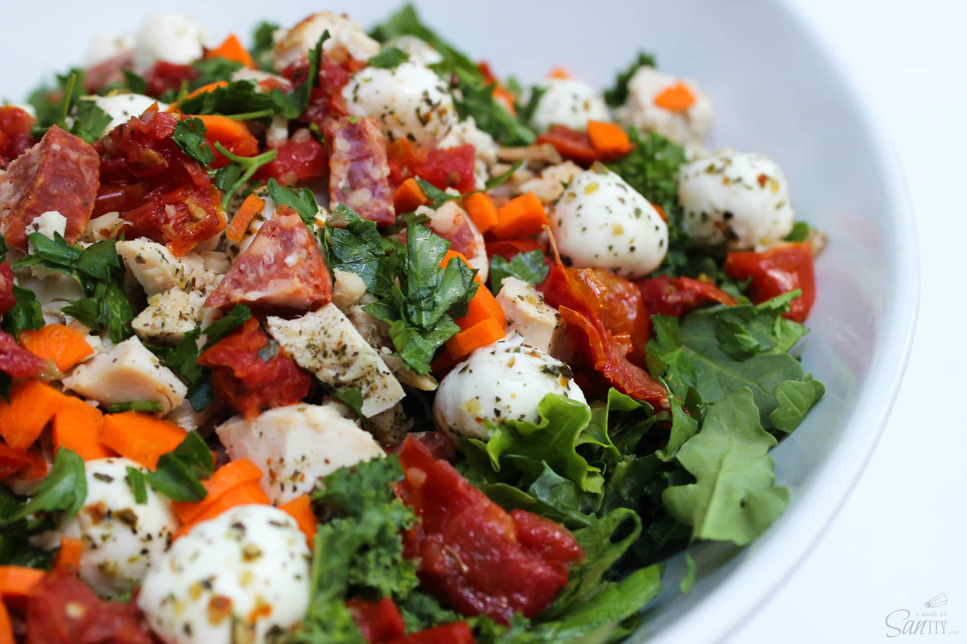 This Italian Kale Salad with Sweet Lemon Garlic Vinaigrette is packed with flavor with roasted tomatoes, chicken, pastrami, and fresh mozzarella cheese.