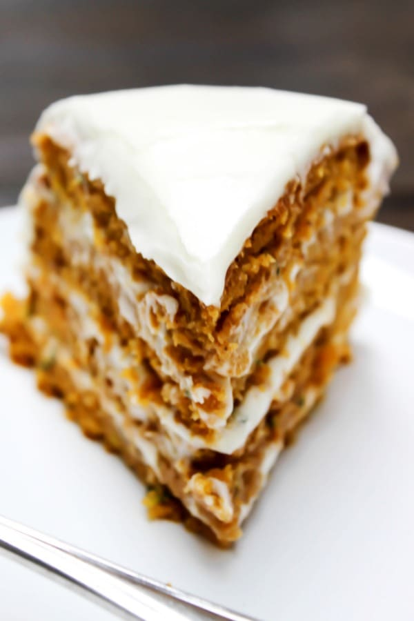 a slice of frosted zucchini pumpkin cake on a plate.