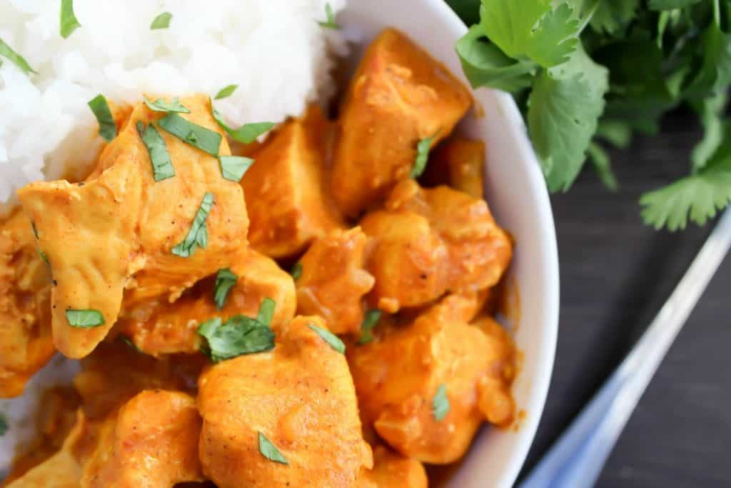 Slow Cooker Butter Chicken up close in a bowl with white rice and cilantro