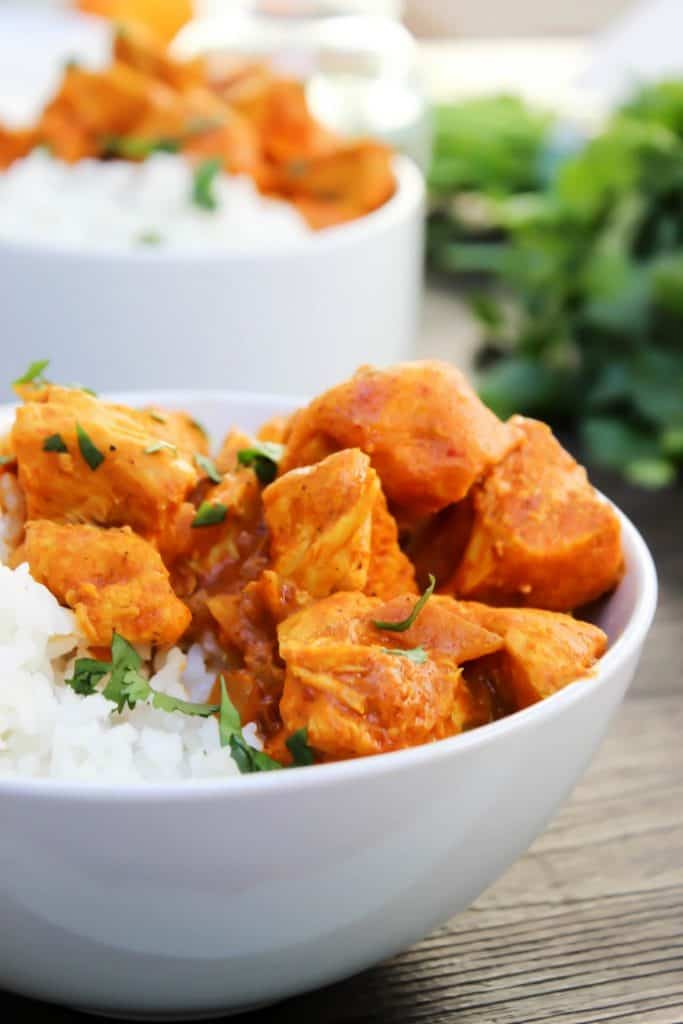 Slow Cooker Butter Chicken in a white bowl with rice