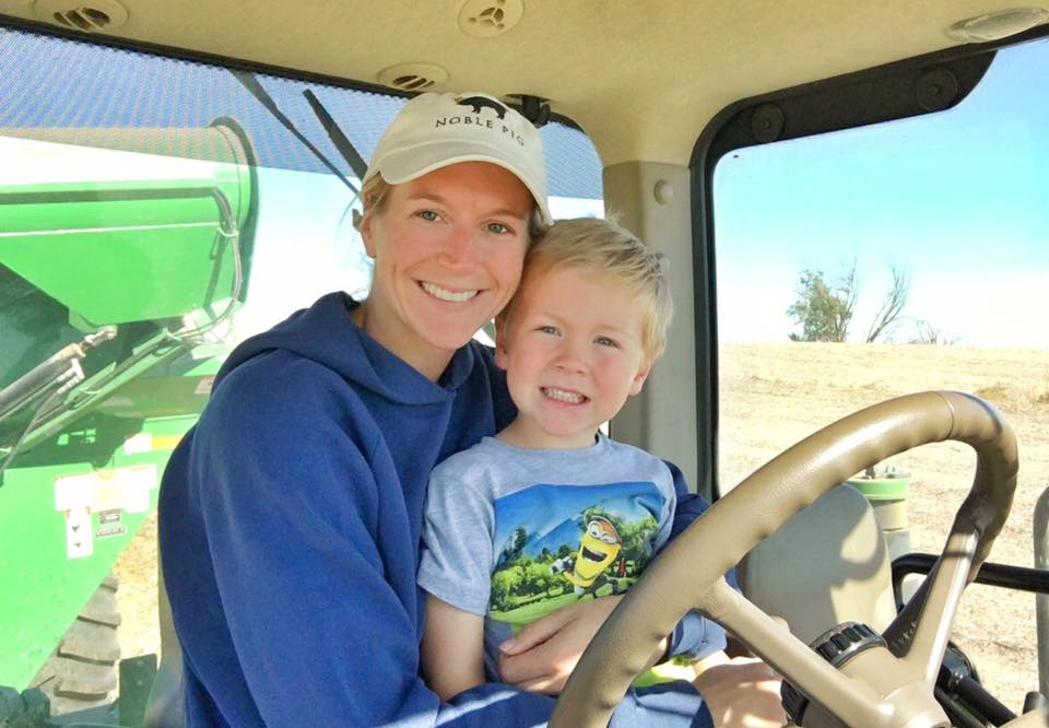 a woman with a young boy on her lap sitting in the driver seat of a tractor