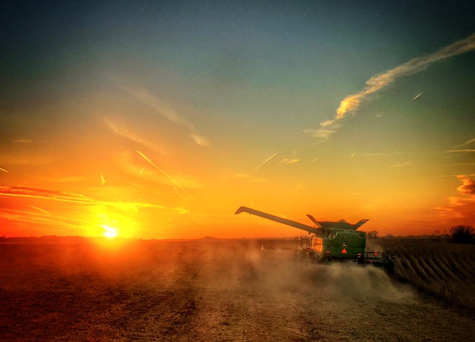 sunrise on farm with tractor spraying a field