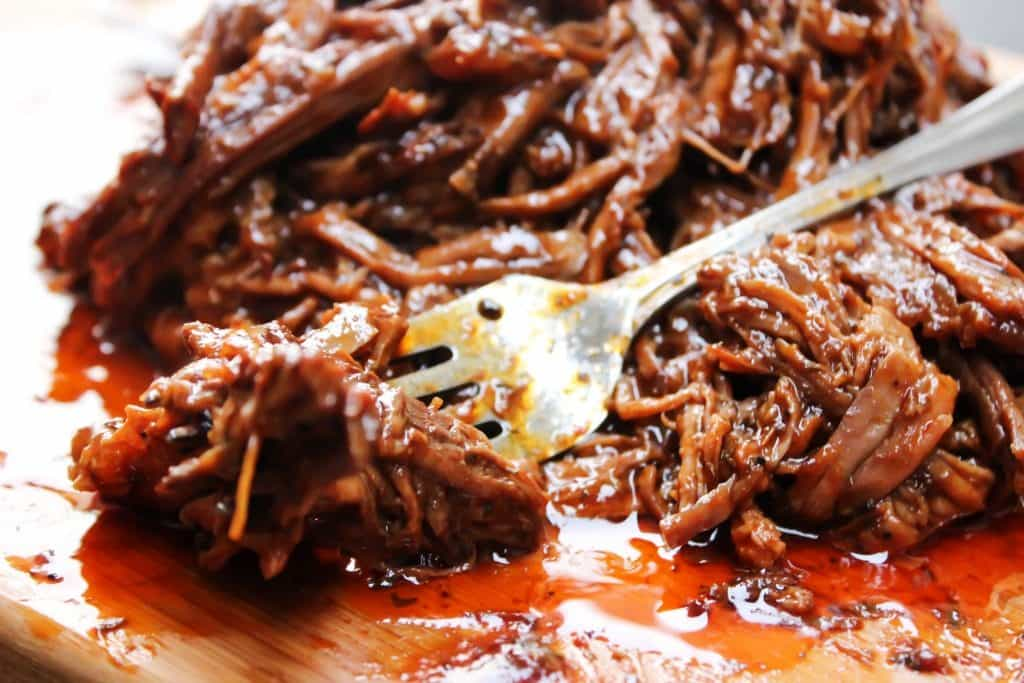 photo of Easy Barbecue Beef Brisket on cutting board with fork