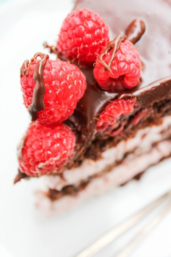 close up photo of ganache and raspberries on top of slice of chocolate raspberry layer cake