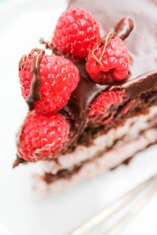 close up photo of ganache and raspberries on top of slice of chocolate raspberry layer cake