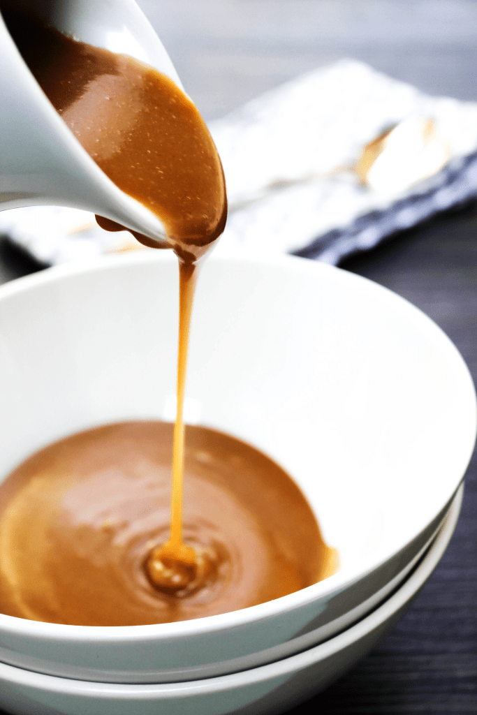 Peanut Butter Caramel Sauce being poured into a serving bowl
