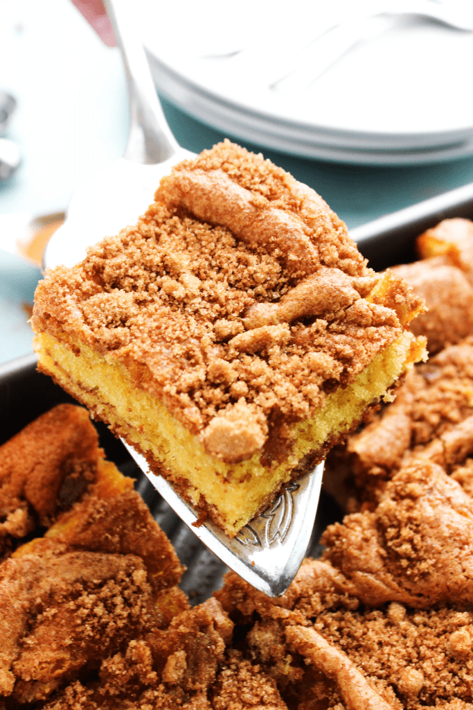 Coffee Cake up close slice on a metal spatula, being held over pan
