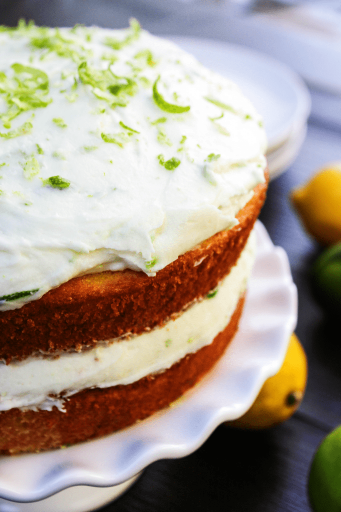Two layered lemon cake with lemon lime buttercream frosting on top, on a white cake stand