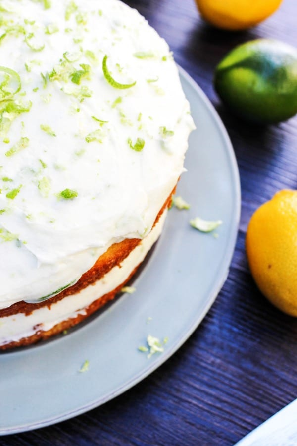 Overhead view of lemon cake with layered lemon and lime buttercream frosting on a white plate, with lime zest on top