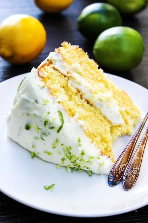 Slice of two layer lemon cake with lemon lime buttercream frosting on a white plate with forks. Lemons and limes on table in background