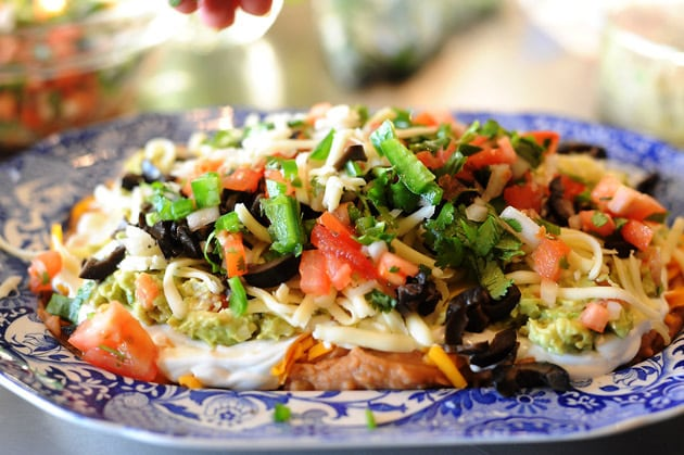 Mexican Layer Dip layed sour cream, refried beans, guacamole, cheese, olives, pico de gallo, jalapenos