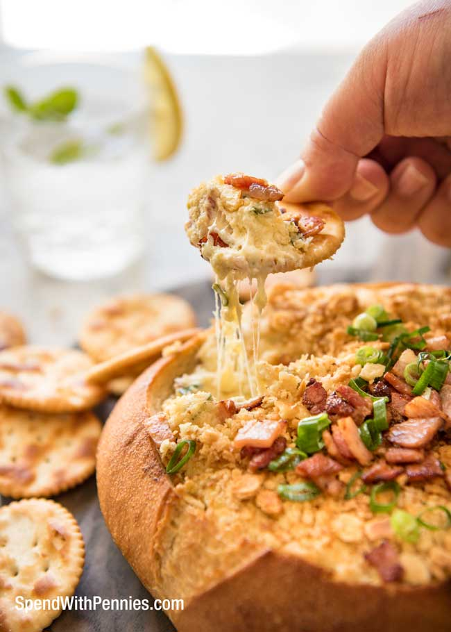 Warm Bacon Cheese Dip in bread bowl with crackers and scallions