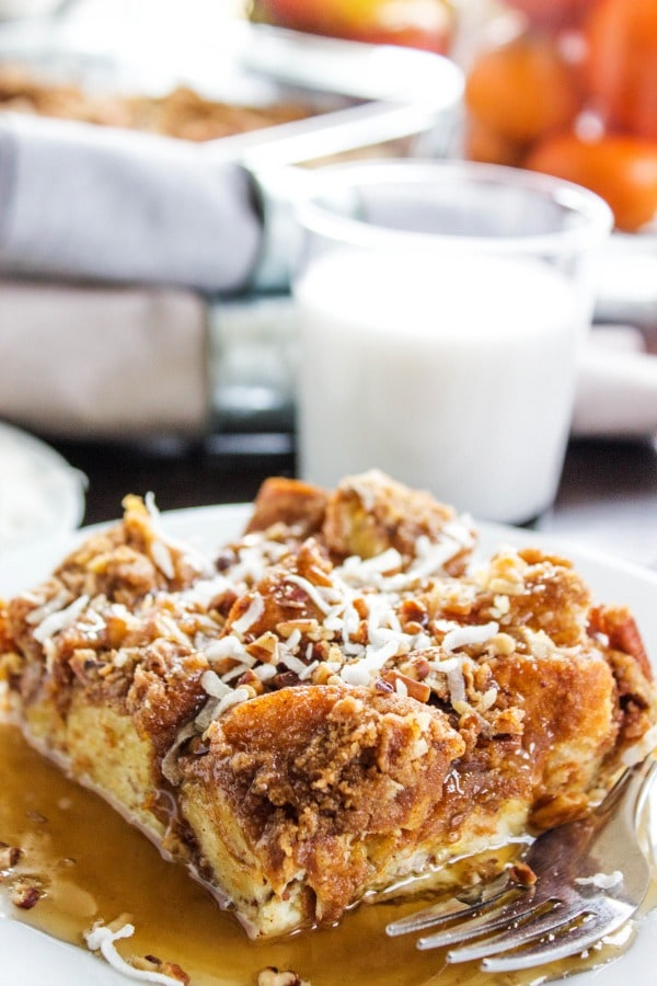 photo of a slice of Overnight Coconut Cinnamon Pecan French Toast Casserole on a plate with syrup, a glass of milk in background