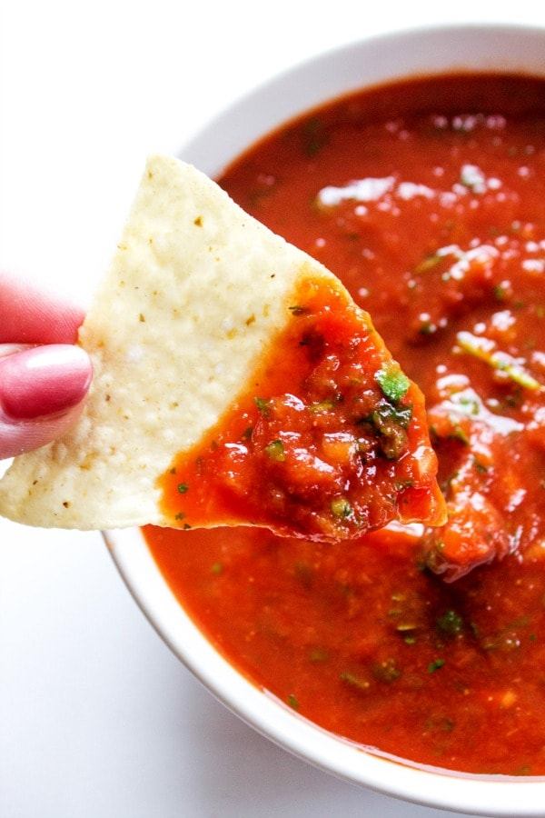 This Best Ever 5-Minute Salsa is an easy to make yet delicious salsa. It is perfect on tacos, or as a snack with your favorite chips..- white bowl, white table, chip with salsa