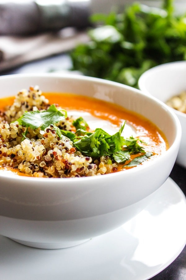 side view photo of Thai Curry Red Pepper Quinoa Soup in a white bowl, with garnish