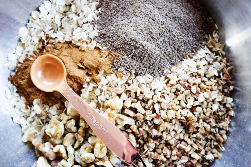 Maple Pecan Granola is a healthier granola option, great as a snack or topping on yogurt. It will quickly become a family favorite.- Ingredients in metal bowl, Copper measuring spoon