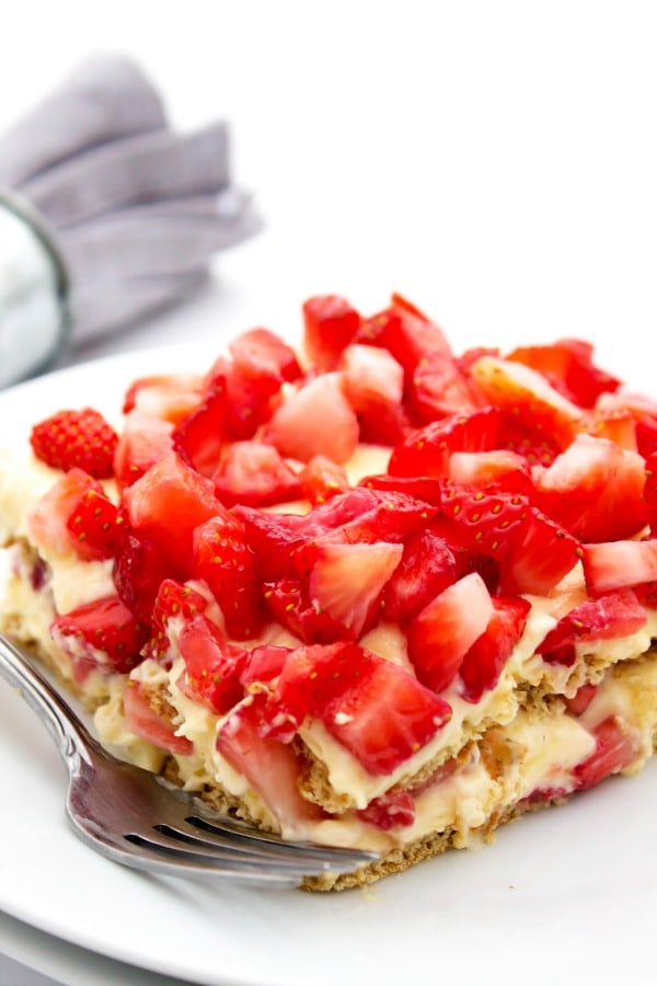 photo of a no bake strawberry cheesecake ice box cake on a white plate with a fork