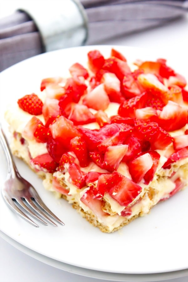 photo of a square slice of no bake strawberry cheesecake ice box cake on a white plate with a fork